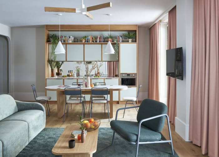 An open plan kitchen, diner and living room space with large windows, wall mounted TV and sage green décor for accommodation