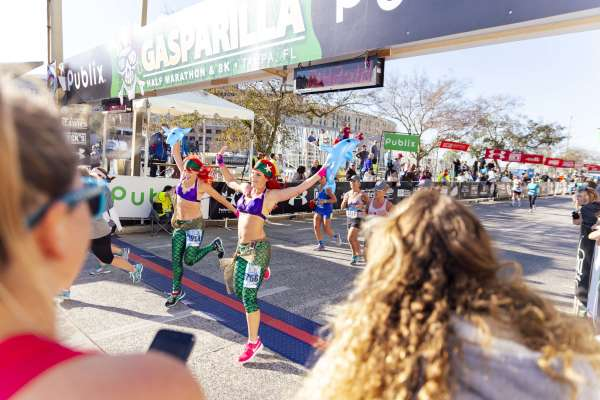 Two mermaid-themed runners crossing the finish line at the Gasparilla Distance Classic
