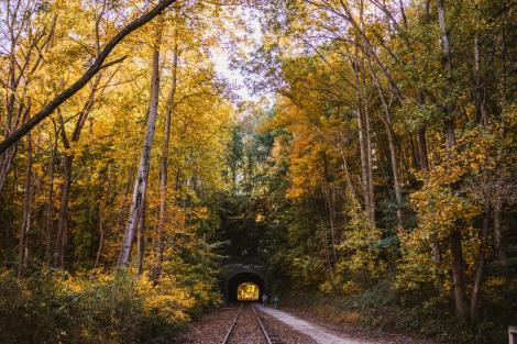 A couple bikes through the historic Howard Tunnel on the rail trail during autumn