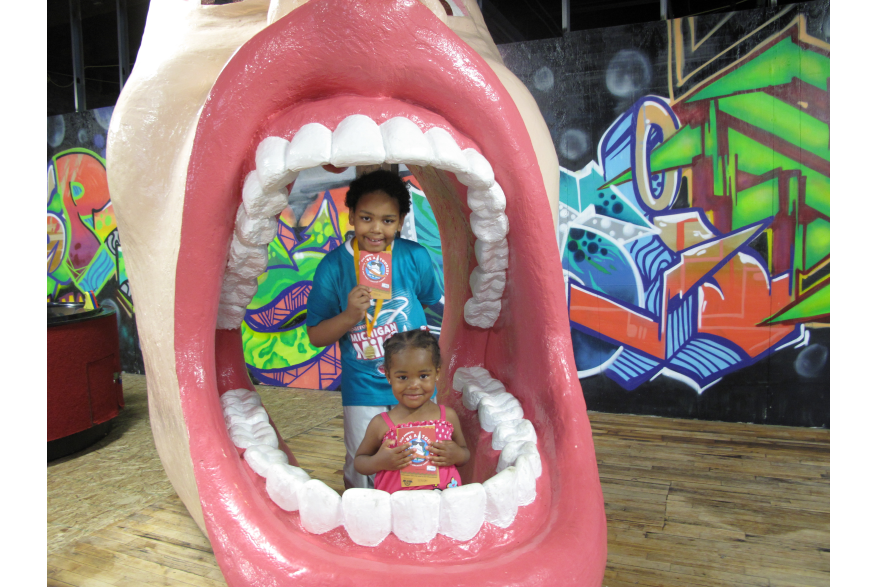 Kids pose for a picture in the Big Mouth at Impression 5 Science Center During Be A Tourist In Your Own Town