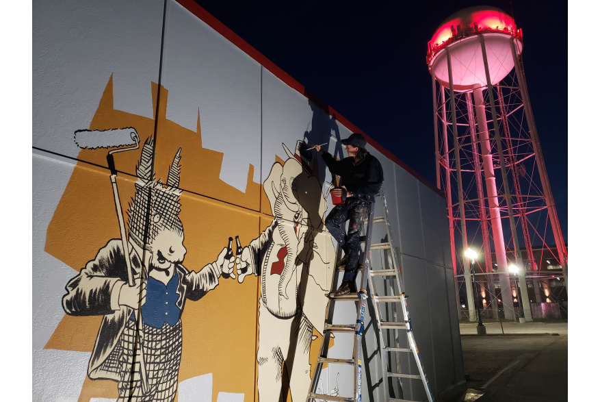 Artist on ladder painting mural with old water tower in background