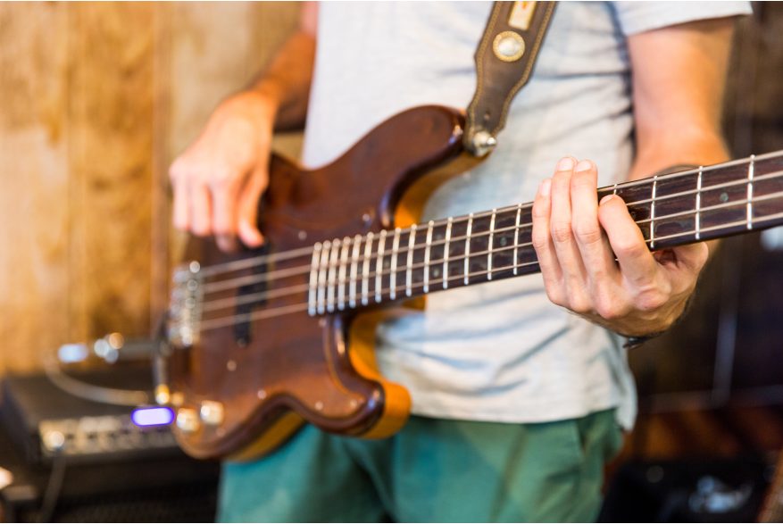 A close up of a guy strumming a brown guitar.