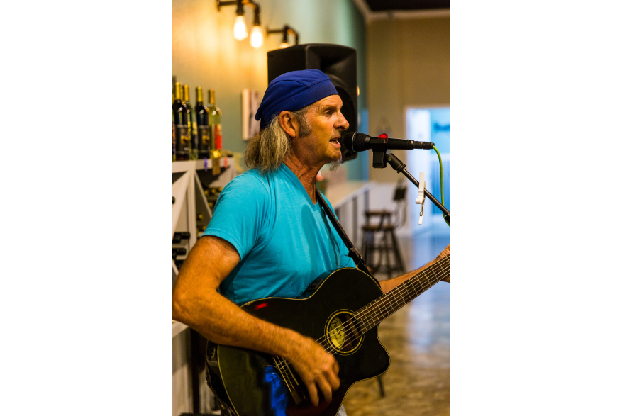 A man in a light blue shirt and dark blue hat strums a guitar and sings into a microphone.