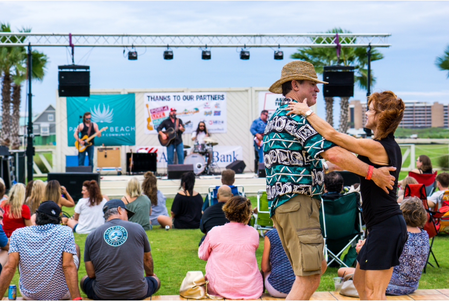 A couple dances in front of a stage where a band is performing. A crowd sits in the grass.