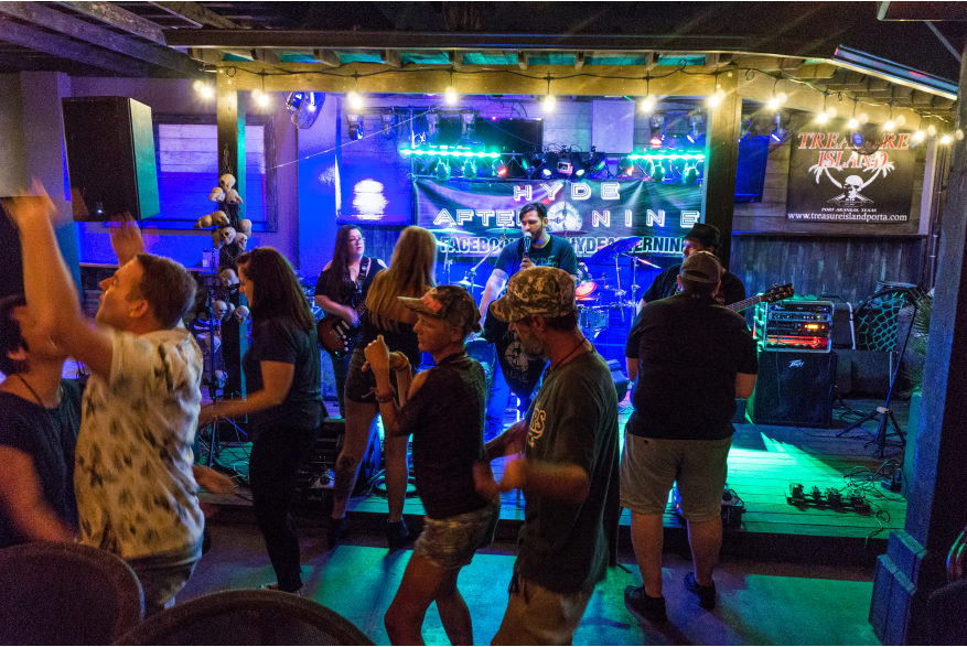 A group dances in front of a band playing on a small stage.