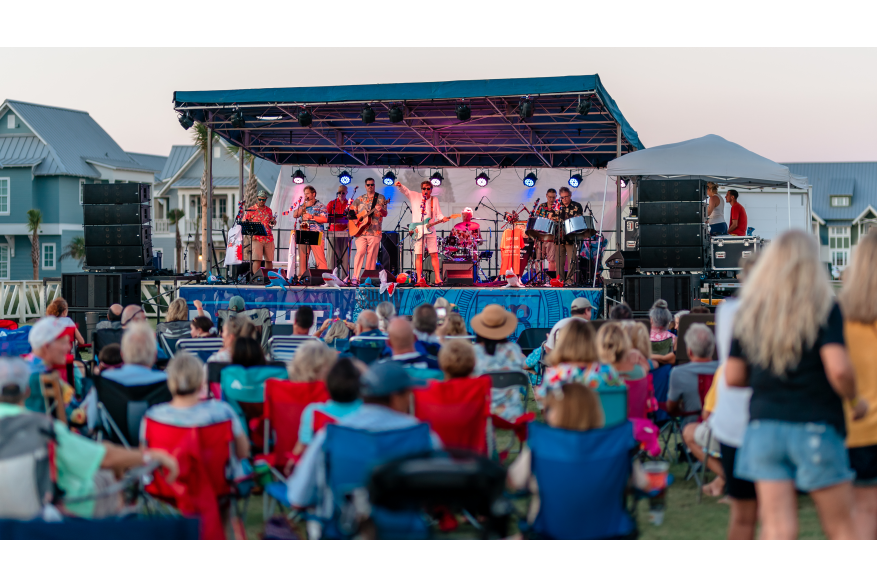 A band plays on a stage while a crowd of people in lawn chairs observes.