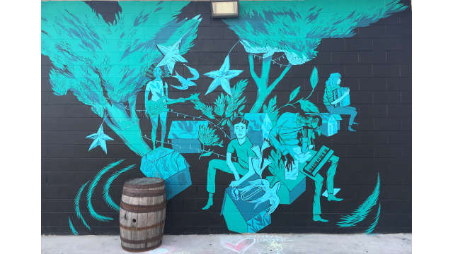 A black and blue mural by Anthony Wislar on the side of Creature Comforts Brewing