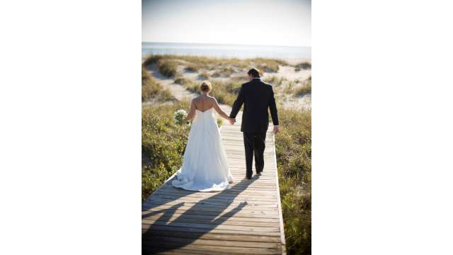 married couple walking on board walk