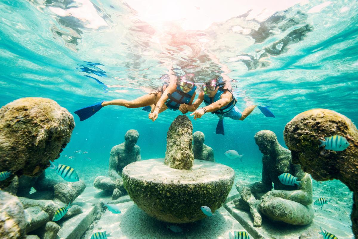 Snorkelers looking at underwater sculptures